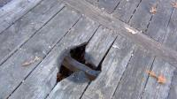 Hole in deck: Hole in deck caused by tenant using fire pit on a wooden deck.